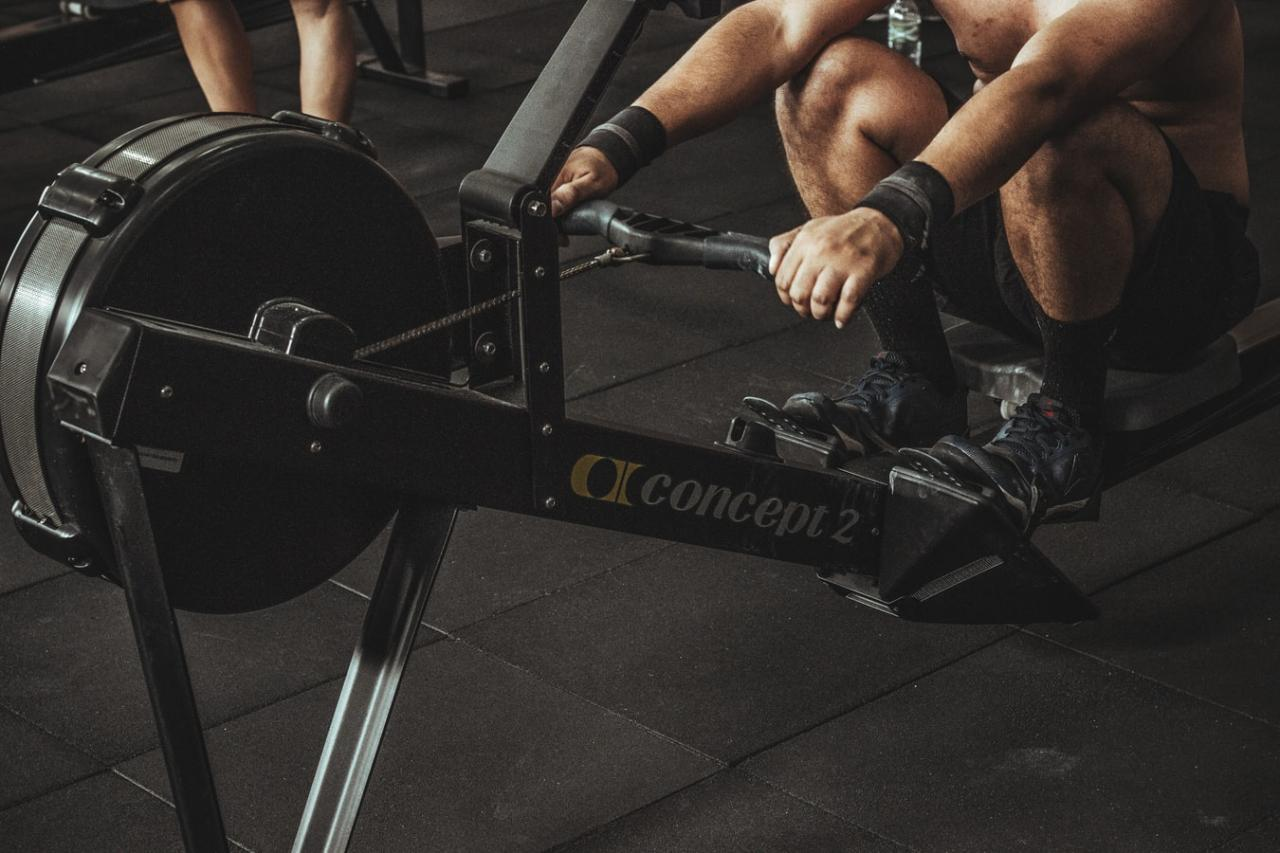 Marine using row machine for strength and contioning